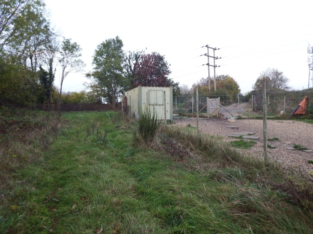 Looking north. The site is behind container with bund beyond. Access track is to right of Electricity poles.
